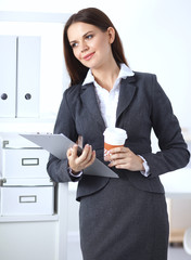 Attractive young businesswoman standing near desk with folder in