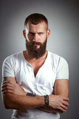 Portrait of handsome bearded man standing with crossed arms