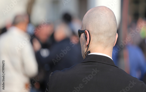 robust security guard with the headset and black glasses - 79996673