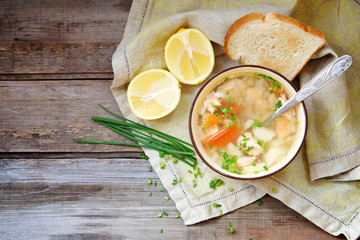 Rustic fish soup in a bowl on a wooden background