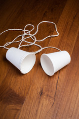 classic paper cup phone on wood background