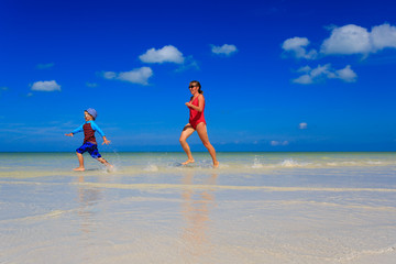 mother and son running in water on summer beach