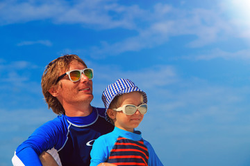Father and little son at the beach on sky