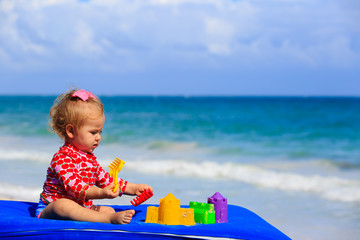 cute little girl playing with toys on the beach