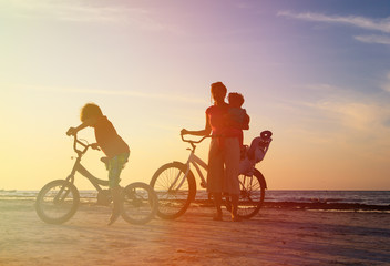 happy mother with kids biking at sunset