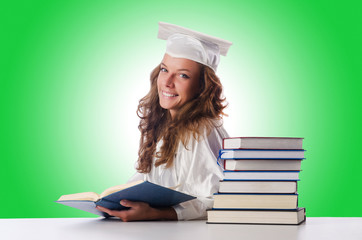 Happy graduate with lots of books on white