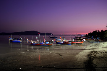 boats on the beach at night in phuket.