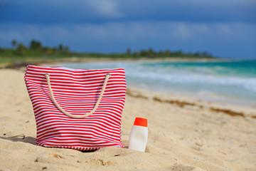 bag and suncream on tropical beach