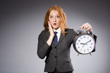 Businesswoman with clock being late for her deliverables