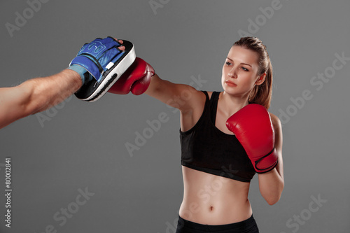 Fototapeta beautiful woman is boxing on gray background