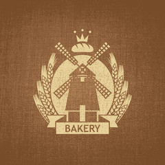 bakery with a mill and a wreath of wheat on fabric background