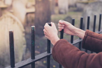 Hands holding fence at graveyard