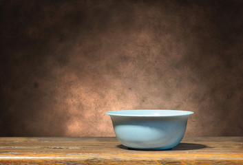 Blue bowl on brown grunge background