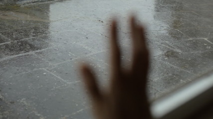 Rainy day hand on window