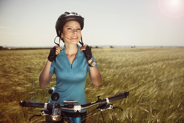 Cheerful beautiful young woman with a bike on a field fastens he