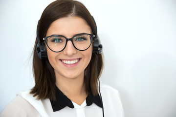 Cheerful businesswoman with headset over gray background