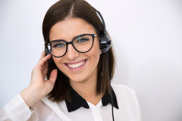 Smiling businesswoman with headset over gray background