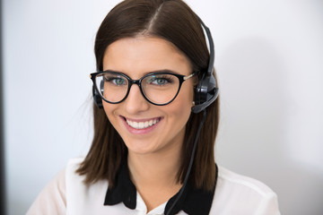 Happy female support operator in headset looking at camera