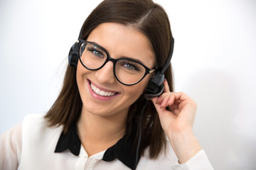 Cheerful female support operator in headset looking at camera