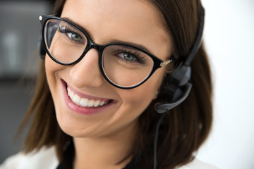 Closeup portrait of a happy female support operator in headset