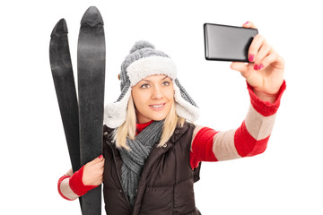 Woman holding a pair of skis and taking selfie