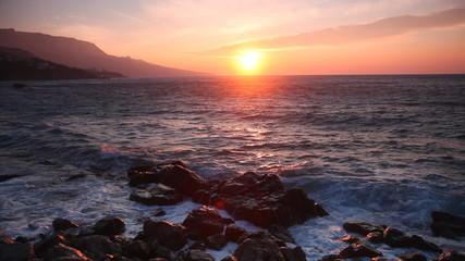 Waves with big splashes break about coastal stones at sunrise