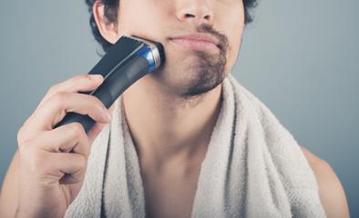 Young man shaving half of his beard