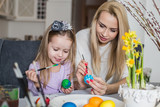 Loving mother and her daughter painting easter eggs