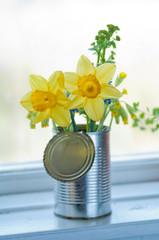 en bukett med påskliljor i en konservburk står på fänsterkarmen