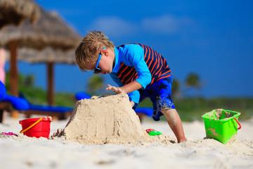 little boy building sandcastle on summer beach