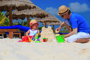 father and little daughter building sandcastle on the beach