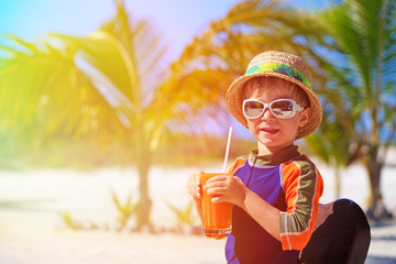 cute little boy drinking juice on tropical beach