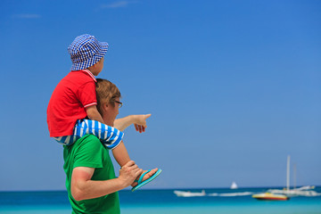 father and little son on shoulders at summer beach