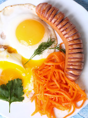 Breakfast fried scrambled eggs with sausage and carrots