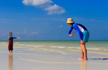 Father and son playing with flying disk at the beach