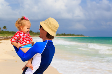 father and little daughter on summer beach