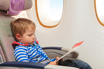 little boy looking at safety instruction in flight