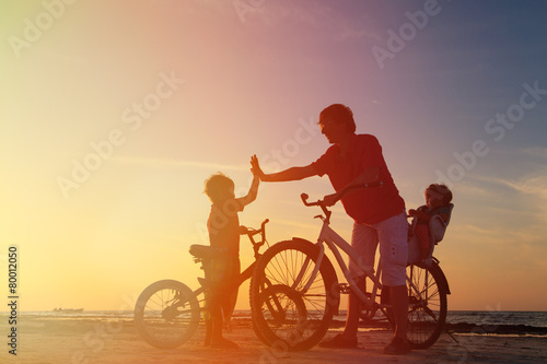 Biker family silhouette, father with two kids on bikes - 80012050
