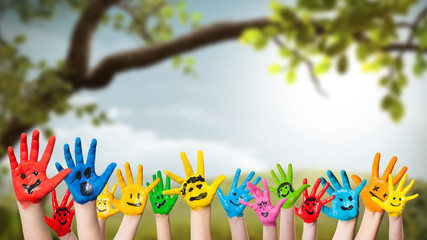 angemalte Kinderhände vor Frühlingshintergrund