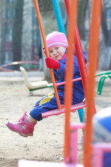 Toddler girl in demi-season warm cloths on playgrounds swing
