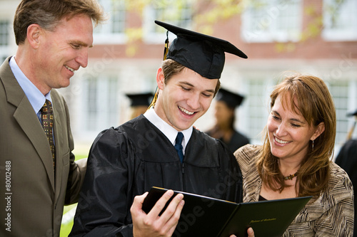Graduation: Proud Family Admires Diploma - 80012488