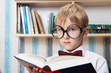 Portrait of a serious boy in bow tie with a book