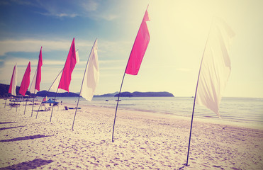 Retro filtered picture of flags on a beach.