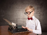 Boy with the old typewriter. Retro style portrait