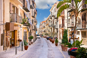Old mediterranean steet with tourist in Cefalu, medieval city of