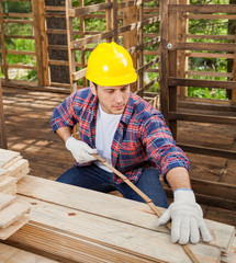 Construction Worker Measuring Wooden Plank At Site