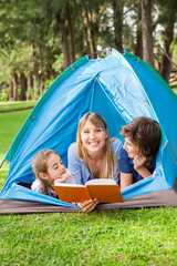Mother Reading Book For Children At Campsite