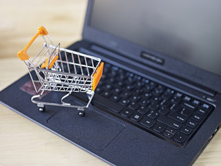 toy shopping cart on top of keyboard of laptop computer