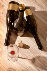 bottles with wine and empty wine glass