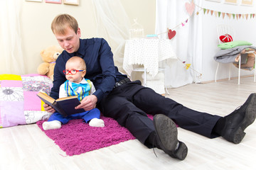 Father and little son read an old book sitting on the carpet